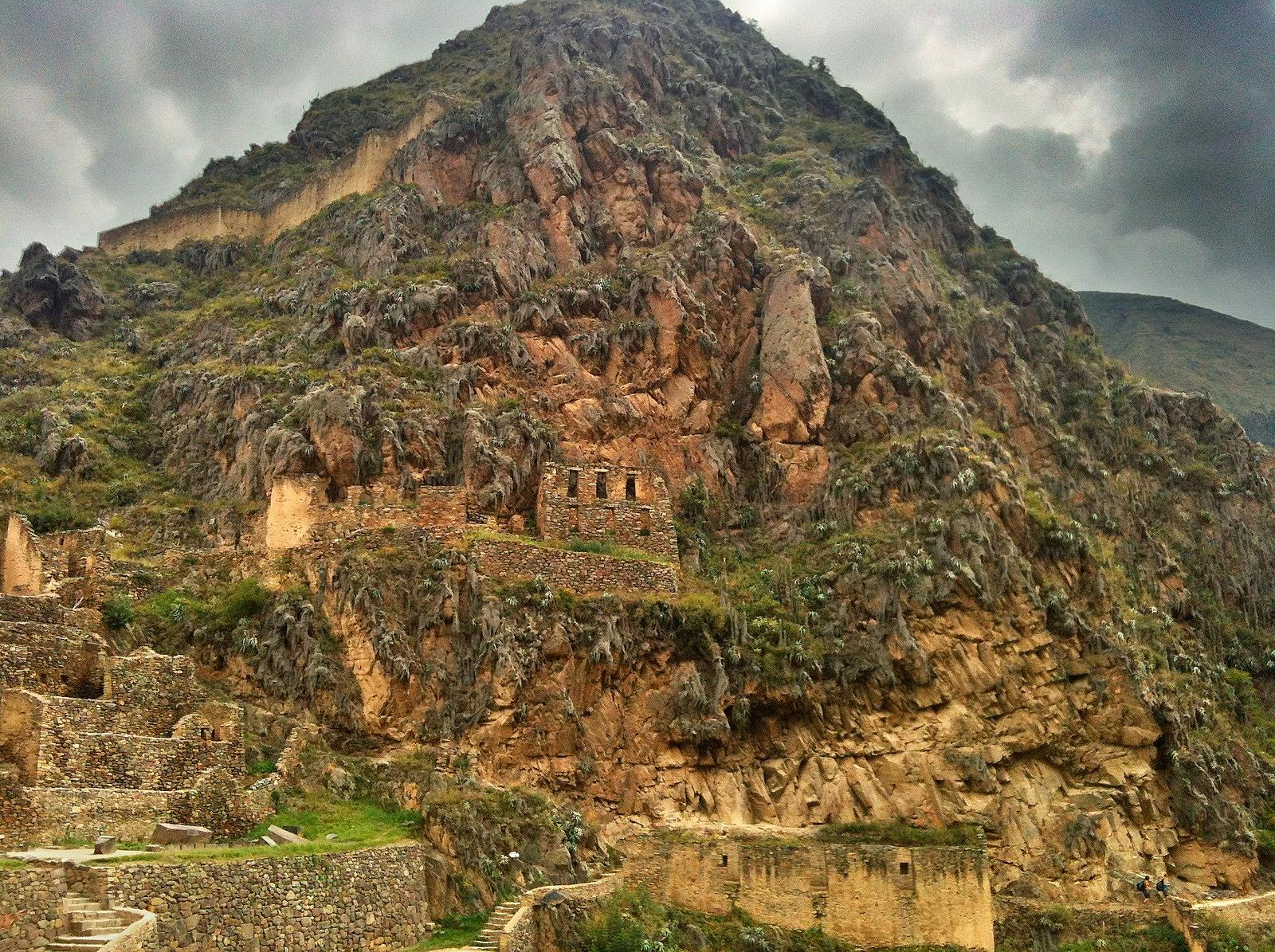 A green mountain inset with yellow brickwork rises in the ancient town of Ollantaytambo.
