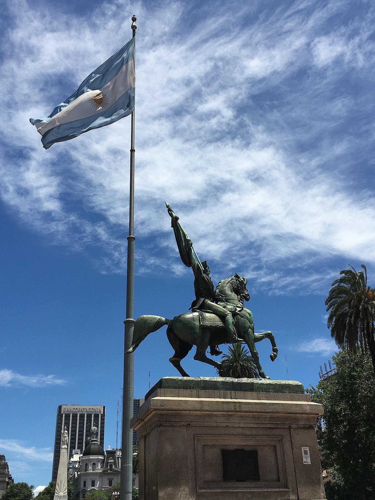 A statue of some army fellow riding atop a horse. Behind and above him flies the Argentinian flag.