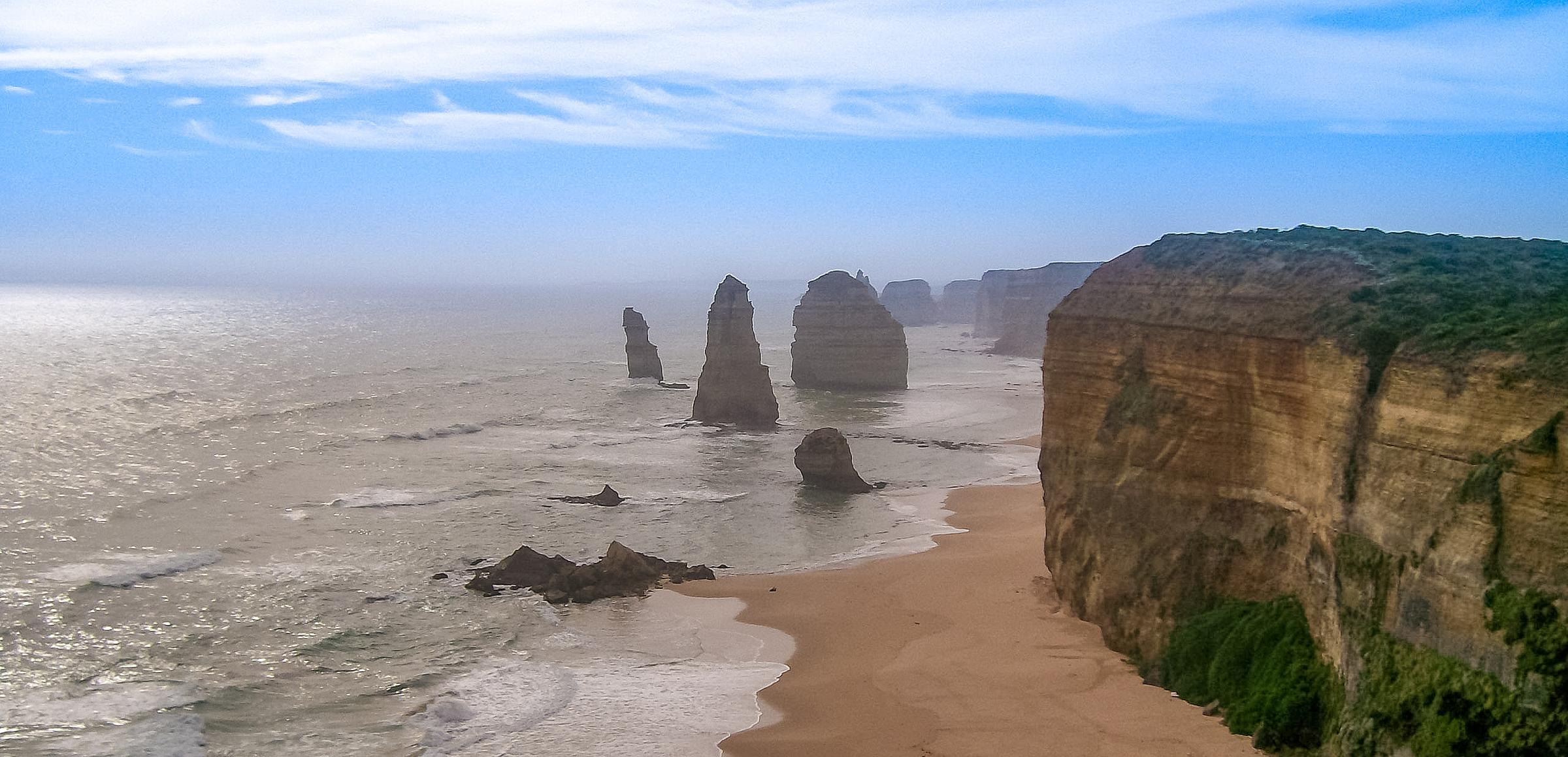 From my previous trip to Melbourne, a view looking out over the cliffs on Great Ocean Road. Several spires rise out of the surf. There were once twelve, but over time, erosion has led several of them to collapse.