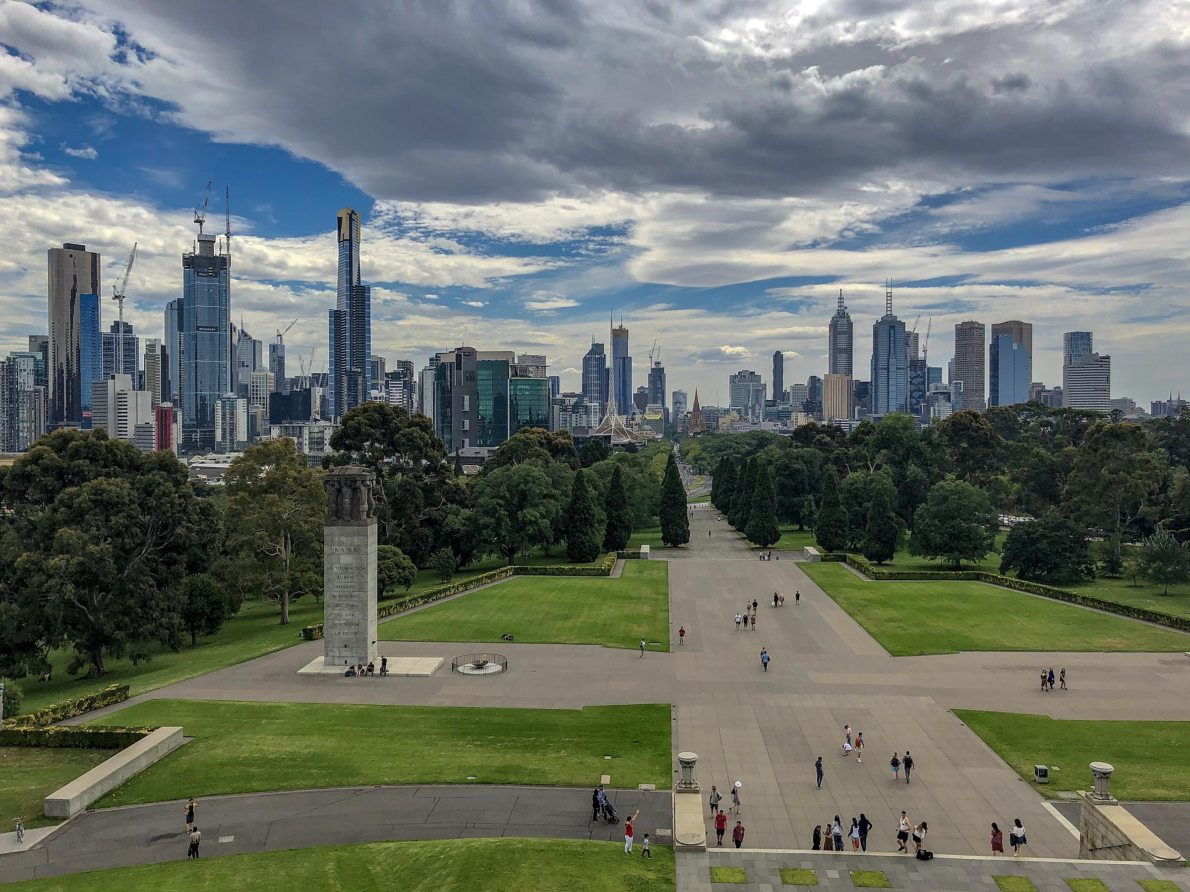 From a high vantage point at the Shrine of Remembrance, looking out over a courtyard with the city of Melbourne's skyline filling the background.