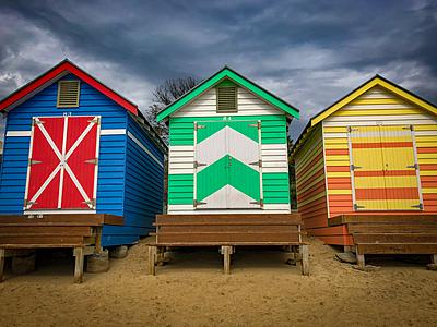 Three brightly colored huts rise from the beach. What goes on in a bathing box? One can only wonder.